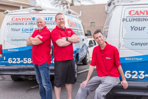 personality photos for canyon state plumbing division where professionals are standing against van and sitting on rear bumper discussing repairs for the day interactive work culture in phoenix az