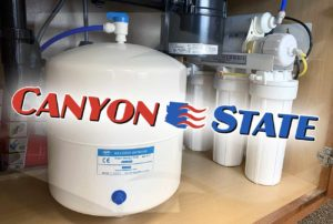 tank for reverse osmosis water purification out of sun city west arizona where canyon state plumbing showroom presents products and equipment for homeowners throughout phoenix metropolitan area filters in background under sink with cabinet doors open